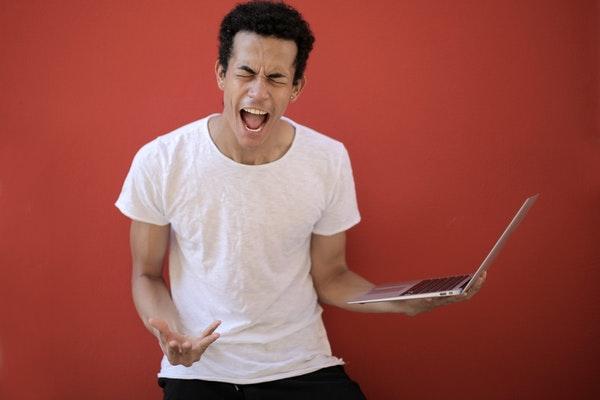 PCをもって叫ぶ男